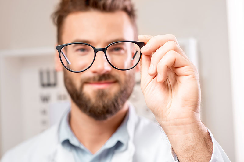 man holding up glasses in front of face
